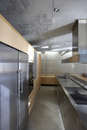Designer kitchen with stainless steel surfaces in concrete h