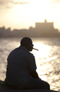 Man in semi silhouette sat on the sea wall at sunset, smoking a cigar, The Malecon, Havana Centro, Havana, Cuba, West Indies, Ce