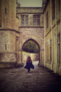 Woman walking through old arch. England, United Kingdom