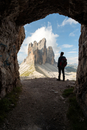 Europe, Italy, Dolomites, Veneto, Belluno. Hiker admire Tre Cime di Lavaredo from Trenches of the First World War on Mount Pater