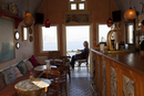 Man on terrace of cafe & bar with coffee, Oia Santorini Cyclades islands, Greece