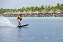 Maldives, Rasdhoo Atoll, Kuramathi Island. A man monoskis past water villas at Kuramathi Island Resort. MR.