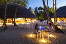 Maldives, Rasdhoo Atoll, Kuramathi Island. A couple enjoy private dining at the Palm Restaurant at Kuramathi Island Resort. MR.