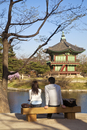 Korea, Seoul, Gyeongbokgung Palace, Couple sitting on bench at Hyangwonjeong Pavilion