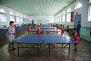A foreign tourist playing table tennis with students at the Dok Song Primary School, North Korea