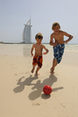 Children playing football in front of the Burj al Arab Hotel, Dubai, United Arab Emirates MR