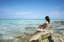 Young woman sitting at the beach, Nagannu island, Kerama islands, Okinawa, Japan