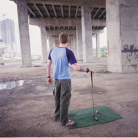 Man Golfing Under Overpass