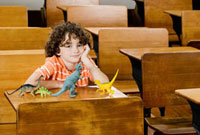 Schoolboy sitting with toys in a classroom 20025296100| 写真素材・ストックフォト・画像・イラスト素材|アマナイメージズ