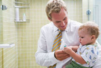 Father Holding Baby and Brushing Teeth
