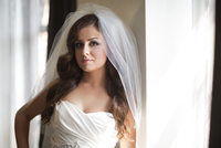 Close-up portrait of bride in wedding gown and veil, looking at camera, Ontario, Canada