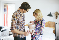 Mom holding newborn, baby boy with Dad standing next to them in bedroom, USA