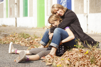 Portrait of mother and daughter sitting on curb on sidewalk in autumn, painted doors of abandoned stables in background, Vendome 20025322761| 写真素材・ストックフォト・画像・イラスト素材|アマナイメージズ