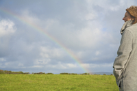 Woman standing in a field looking at the rainbow 20025325065| 写真素材・ストックフォト・画像・イラスト素材|アマナイメージズ