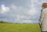 Woman standing in a field looking at the rainbow 20025325066| 写真素材・ストックフォト・画像・イラスト素材|アマナイメージズ