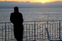 Back view of a man leaning over the railings of a ferry boat looking at the sunset 20025325158| 写真素材・ストックフォト・画像・イラスト素材|アマナイメージズ