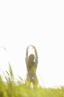 Back View of Woman Standing in a Field with Sun Shining through her Hands 20025326091| 写真素材・ストックフォト・画像・イラスト素材|アマナイメージズ