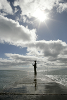 View of a man standing in the sea with his laptop. 20025326472| 写真素材・ストックフォト・画像・イラスト素材|アマナイメージズ