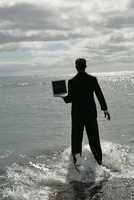 View of a man standing in the sea with his laptop. 20025326473| 写真素材・ストックフォト・画像・イラスト素材|アマナイメージズ