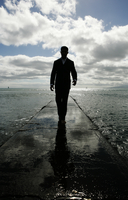 View of a man standing walking on a pier. 20025326475| 写真素材・ストックフォト・画像・イラスト素材|アマナイメージズ