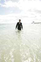 View of a man standing in the sea. 20025326480| 写真素材・ストックフォト・画像・イラスト素材|アマナイメージズ