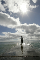View of a man standing near the sea with his laptop. 20025326481| 写真素材・ストックフォト・画像・イラスト素材|アマナイメージズ