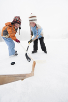 Italy, South Tyrol, Seiseralm, Two Boys playing ice hockey