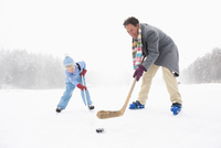 Italy, South Tyrol, Seiseralm, Father and son (4-5) playing ice hockey