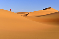 Algeria, Sahara, Tassili N'Ajjer National Park, Tadrart, woman walking in the dunes of Tehak 20025330173| 写真素材・ストックフォト・画像・イラスト素材|アマナイメージズ