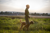 Senior woman walking with her dog over a meadow 20025330857| 写真素材・ストックフォト・画像・イラスト素材|アマナイメージズ