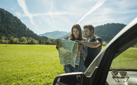 Austria, Tyrol, Tannheimer Tal, young coupe at car looking at map 20025331197| 写真素材・ストックフォト・画像・イラスト素材|アマナイメージズ