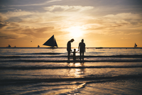 Philippines, Boracay, family with one child at seashore by sunset 20025331346| 写真素材・ストックフォト・画像・イラスト素材|アマナイメージズ