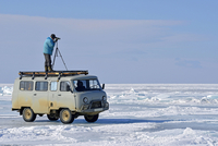 Russia, Lake Baikal, man with telescope standing on minibus on frozen lake looking out for seals 20025331473| 写真素材・ストックフォト・画像・イラスト素材|アマナイメージズ