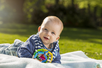 Portrait of smiling baby boy lying on blanket on a meadow 20025331525| 写真素材・ストックフォト・画像・イラスト素材|アマナイメージズ