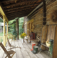 PORCHES - Log Farmhouse porch, wide plank floors, yellow painted porch posts, bucket of sunflowerd, wooden bench withbasket of v 20025340863| 写真素材・ストックフォト・画像・イラスト素材|アマナイメージズ