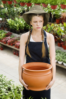 Woman holding a pot in a greenhouse 20025341713| 写真素材・ストックフォト・画像・イラスト素材|アマナイメージズ