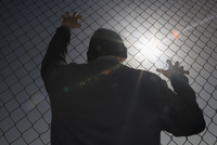 Rear view of a man looking through a chainlink fence 20025341881| 写真素材・ストックフォト・画像・イラスト素材|アマナイメージズ