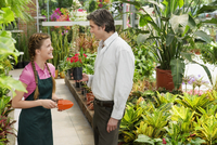 Female planter and a customer in a greenhouse 20025342116| 写真素材・ストックフォト・画像・イラスト素材|アマナイメージズ