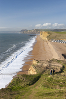 Two walkers enjoy the view along the beautiful vista from the cliffs of Burton Bradstock, looking towards East Cliff, West Bay a 20025366237| 写真素材・ストックフォト・画像・イラスト素材|アマナイメージズ