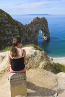 Woman resting on a clifftop sign, looking towards Durdle Door beach, Jurassic Coast, UNESCO World Heritage Site, Dorset, England 20025369294| 写真素材・ストックフォト・画像・イラスト素材|アマナイメージズ