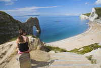Woman resting on a clifftop sign, looking towards Durdle Door beach, Jurassic Coast, UNESCO World Heritage Site, Dorset, England 20025369295| 写真素材・ストックフォト・画像・イラスト素材|アマナイメージズ