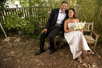 Portrait of happy African American bride and groom sitting on bench outside in nature setting on wedding day, high angle view