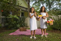 Portrait of happy elementary age African American girls holding flower baskets near picnic blanket in backyard 20025384938| 写真素材・ストックフォト・画像・イラスト素材|アマナイメージズ