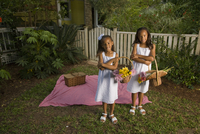 Portrait of happy elementary age African American girls holding flower baskets near picnic blanket in backyard 20025384939| 写真素材・ストックフォト・画像・イラスト素材|アマナイメージズ