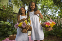 Portrait of happy elementary age African American girls holding flower baskets near picnic blanket in backyard 20025384940| 写真素材・ストックフォト・画像・イラスト素材|アマナイメージズ