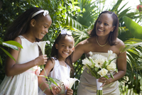 Happy African American bride holding bouquet outside with flower girls on wedding day 20025384951| 写真素材・ストックフォト・画像・イラスト素材|アマナイメージズ