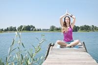 Blond young woman practicing yoga at a lake