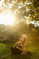 Smiling young woman playing guitar in autumn