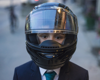 Close-up portrait of a ten year old boy wearing a tie and a motorcycle helmet outdoors on a side walk in Toronto, Ontario, Canad