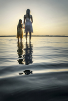 Mother and Daughter facing sunset in river